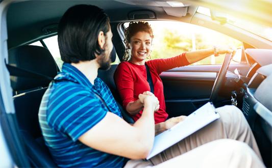 Instruktor i kursantka w pojeździe szkoły jazdy w czasie nauki jazdy na kategorie B