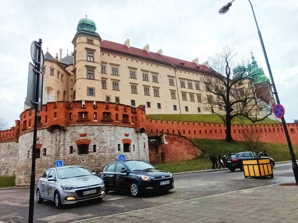 Samochody nauki jazdy Orzeł na tle zamku na Wawelu